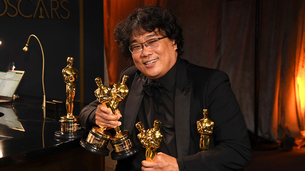 "Bong Joon-ho holds the Oscars for best original screenplay, best international feature film, best directing, and best picture for ""Parasite"" at the Governors Ball after the Oscars,"